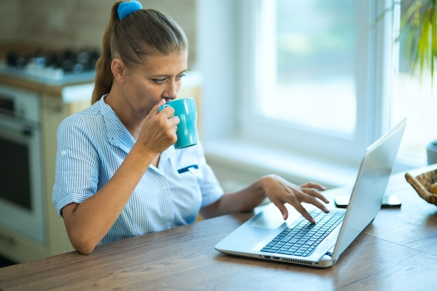Femme au foyer à la maison dans la cuisine est assise à une table avec un ordinateur portable. communique, se détend, travaille à domicile et achats en ligne