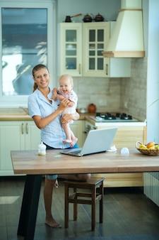 Une femme au foyer à la maison dans la cuisine est assise à table avec un ordinateur portable et un petit bébé. communique, se détend, travaille à domicile et magasine en ligne
