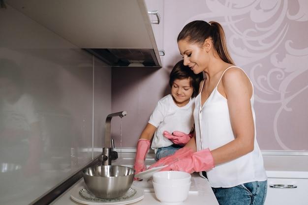 Femme au foyer maman en gants roses lave la vaisselle avec son fils à la main dans l'évier avec un détergent. une fille en blanc et un enfant avec un plâtre nettoie la maison et lave la vaisselle avec des gants roses faits maison.