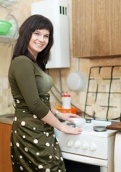 Femme au foyer nettoie la cuisinière à gaz avec une éponge