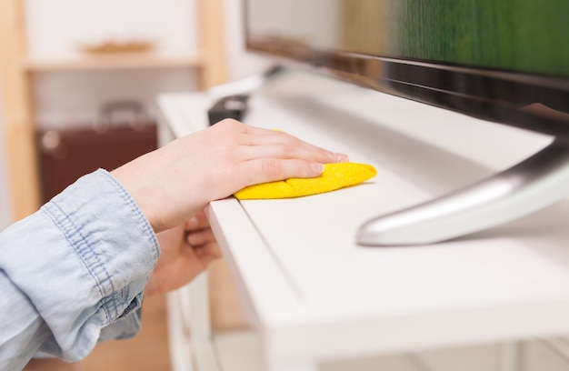 Femme au foyer nettoyant la poussière du meuble tv dans le salon