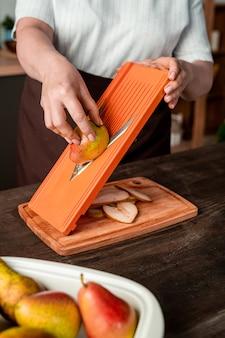 Femme au foyer occasionnelle couper des poires fraîches sur une planche à découper pour les sécher dans un séchoir à fruits électrique domestique en se tenant debout par une table de cuisine