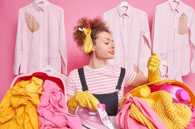 Femme au foyer occupée avec chaussette et pinces à linge dans les cheveux bouclés regarde attentivement à portée de main dans un gant de protection en caoutchouc entouré de paniers à linge fers à repasser des poses de linge près de chemises repassées brûlées sur des cintres