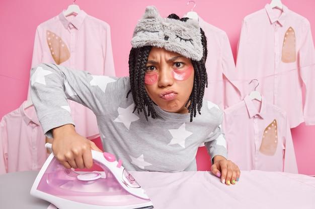 Une femme au foyer occupée et mécontente fait du repassage fait une grimace malheureuse à la caméra vêtue de vêtements de nuit, des vêtements de mari posent contre le mur rose
