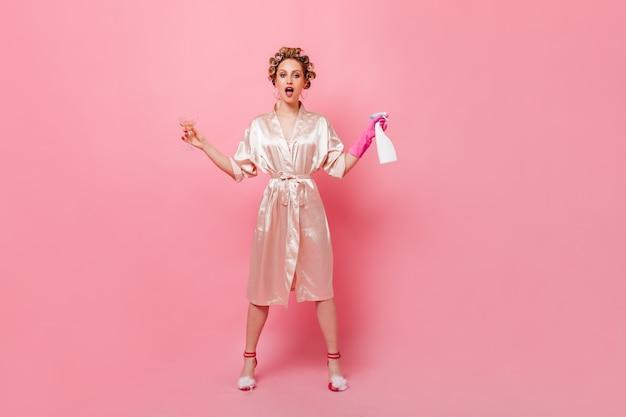 Femme au foyer en peignoir tenant verre à martini et nettoyant pour miroir