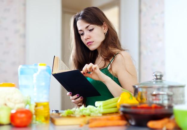 Femme au foyer pensive avec livre de recettes