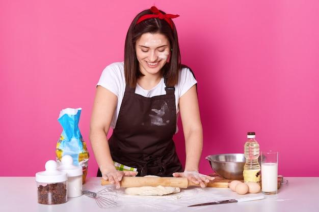 Femme au foyer pétrit joyeusement la pâte avec un rouleau à pâtisserie.