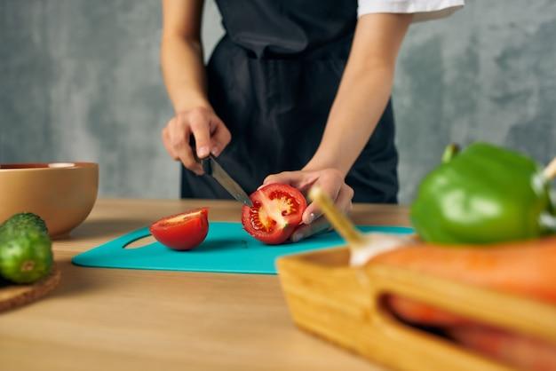 Femme au foyer sur la planche à découper de légumes de coupe de cuisine