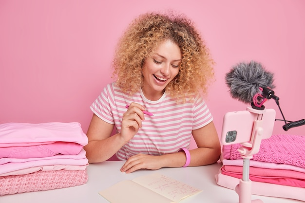 Une femme au foyer positive aux cheveux bouclés prend des notes dans le bloc-notes écrit des informations sur la façon de s'occuper des enregistrements de lessive. la vidéo en direct est assise à table près de deux tas de vêtements pliés isolés sur du rose