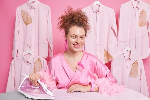 Une femme au foyer positive aux cheveux bouclés vêtue d'une robe domestique utilise un fer électrique occupé à caresser tous les vêtements de famille lavés pose à la buanderie se sent heureuse d'une journée bien remplie. concept de routines d'entretien ménager