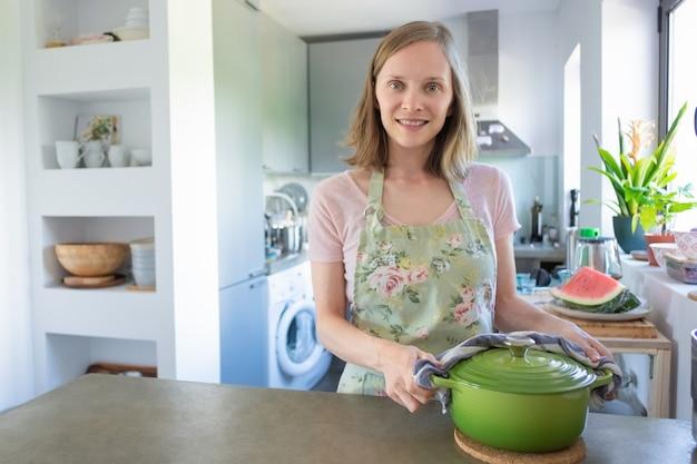 Femme au foyer positive cuisine dans sa cuisine, tenant une casserole chaude avec une serviette, regardant la caméra et souriant. concept de cuisine à la maison