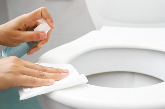 Femme au foyer pulvérisant un désinfectant sur les toilettes covid-19