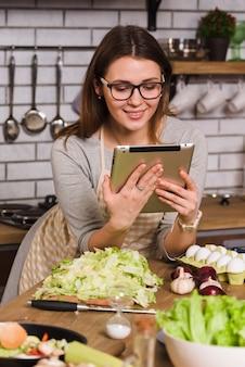Femme au foyer en regardant une tablette debout dans la cuisine