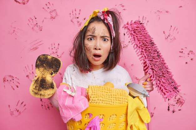 La femme au foyer regarde avec la bouche largement ouverte choquée d'avoir beaucoup de travaux ménagers tient des outils de nettoyage range la pièce se tient près du panier à linge sur rose