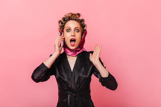 Femme au foyer en robe de chambre et écharpe regarde devant avec étonnement et parle au téléphone