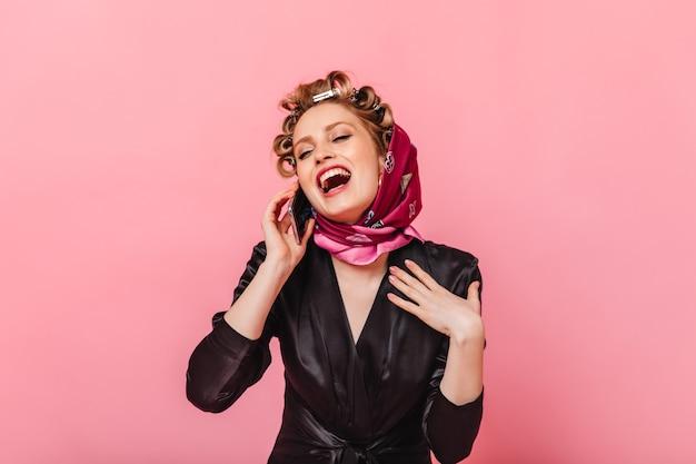 Femme au foyer en robe de chambre noire rit et parle au téléphone sur le mur rose