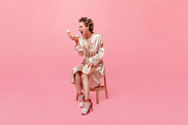 Femme au foyer en robe de chambre et en sandales sur le talon est assise sur une chaise et crie au téléphone