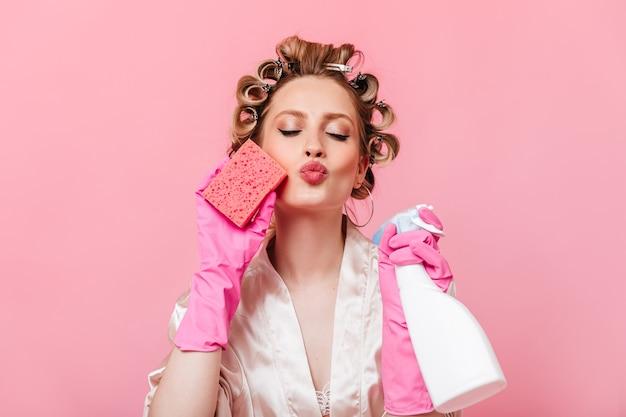 Femme au foyer en robe rose et gants en caoutchouc envoie un baiser