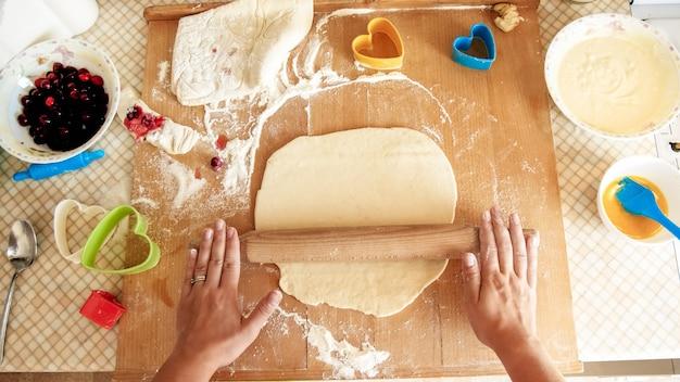 Femme au foyer rouler la pâte avec un rouleau à pâtisserie en bois
