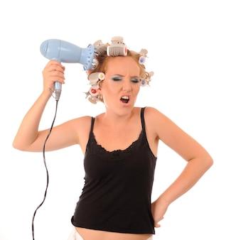 Femme au foyer avec un sèche-cheveux