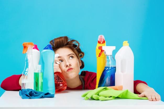 Femme au foyer semble fatiguée et plongée dans ses pensées pendant le nettoyage et le lavage