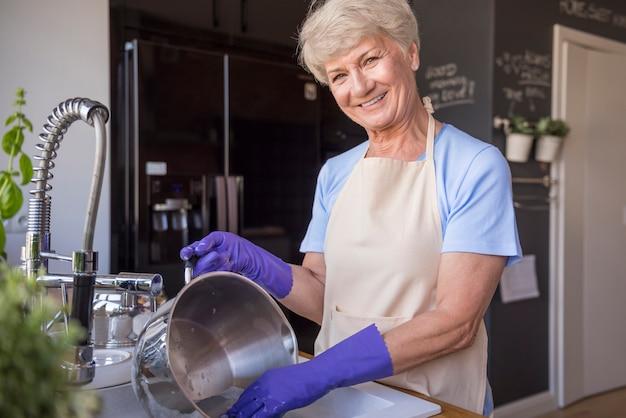 Femme au foyer senior gaie dans la cuisine