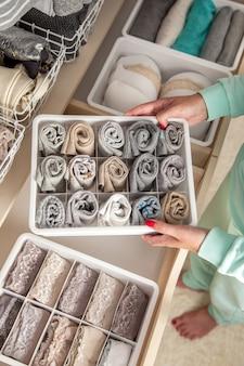 Une femme au foyer soignée non identifiée met un conteneur avec des chaussettes, des culottes et des sous-vêtements. stockage de vêtements.