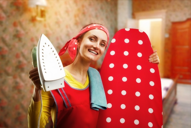 Femme au foyer souriante avec planche et fer à repasser