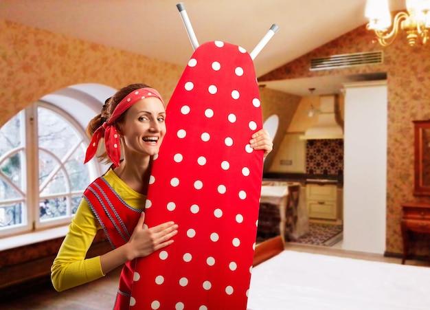 Femme au foyer souriante avec planche à repasser