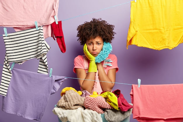 Femme au foyer surmenée bouleversée suspend ses vêtements sur une corde à linge avec des pinces à linge
