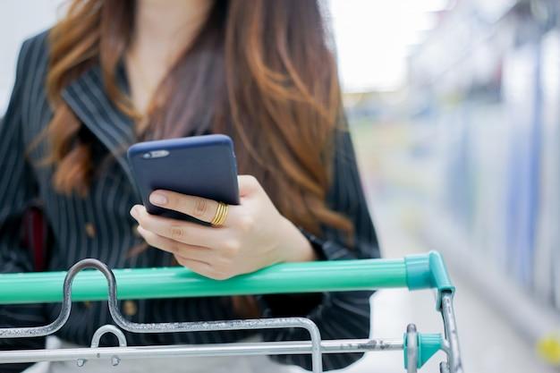 Femme au foyer tenant smartphone pour la liste de contrôle au concept de supermarché
