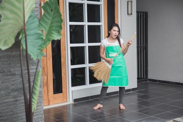 Femme au foyer tenir un balai et sourire