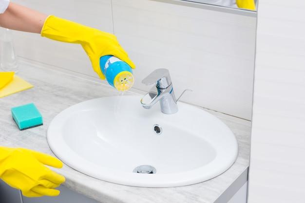 Femme au foyer vidant une poudre à récurer dans un lavabo à partir d'une bouteille en plastique avec des mains gantées dans un concept de santé et d'hygiène
