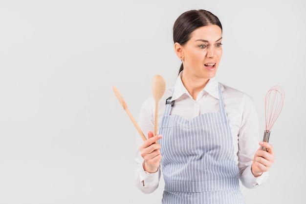 Femme au foyer avec visage surpris en regardant fouet
