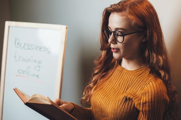 Femme au gingembre avec des lunettes lit un livre pendant les cours de commerce en ligne