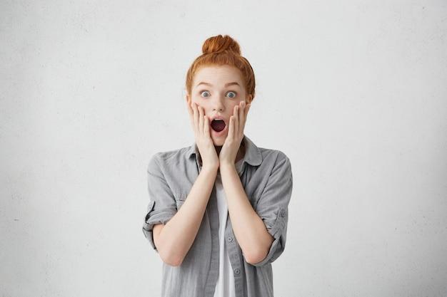 Femme au gingembre surprise aux yeux bleus et taches de rousseur soulevant les sourcils, regardant avec de grands yeux et la bouche largement ouverte étant en panique, inquiète d'entendre de mauvaises nouvelles. femme horrifiée avec un regard effrayé choqué
