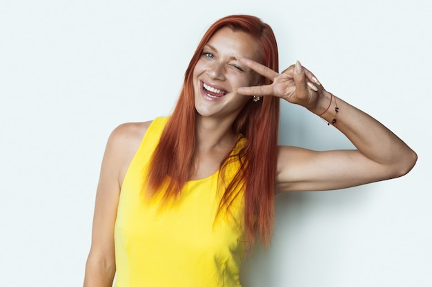 Femme au gingembre avec des taches de rousseur sourit montrant sa langue faisant des gestes le signe de la paix sur un mur de studio blanc portant une robe jaune