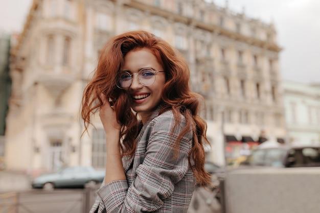 Femme au gingembre en veste grise à carreaux souriant à l'extérieur
