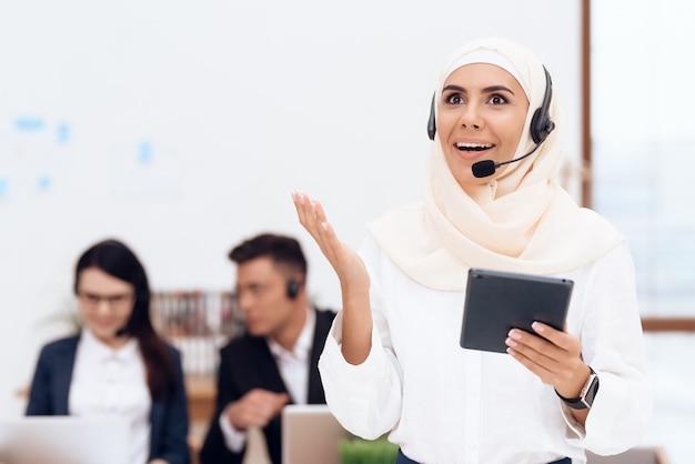 La femme au hijab se tient dans le centre d'appels
