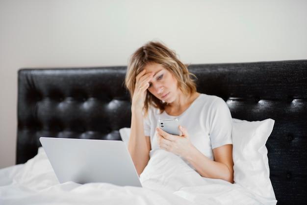 Femme au lit à l'aide d'un ordinateur portable et mobile
