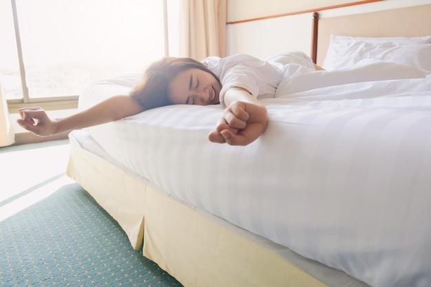 Femme au lit essayant de se réveiller