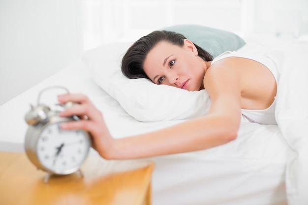 Femme au lit, étendant la main au réveil