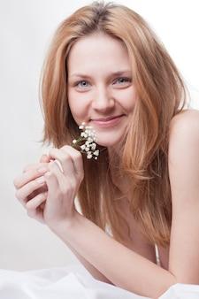 Femme au lit avec une fleur