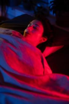 Femme au lit avec des lumières de chambre mystérieuses