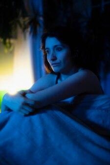 Femme au lit à la maison avec des lumières mystérieuses autour d'elle
