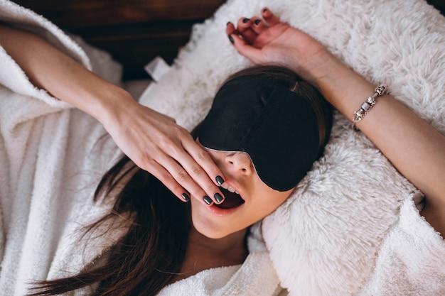 Femme au lit avec masque de sommeil