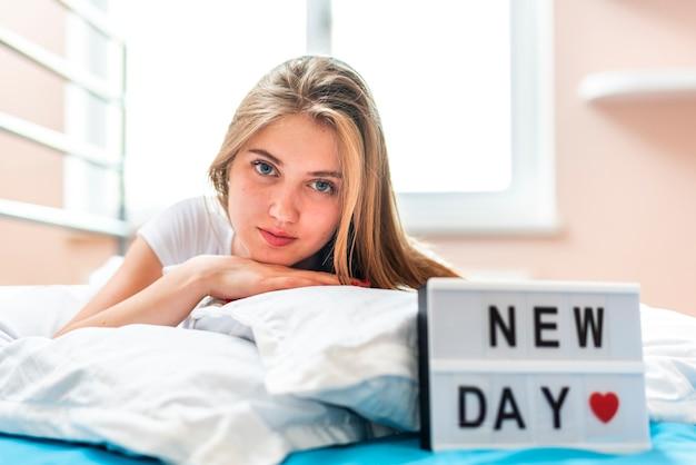 Femme au lit en regardant la caméra