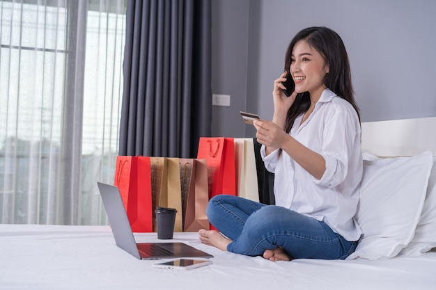 Femme au lit, shopping en ligne avec smartphone et carte de crédit