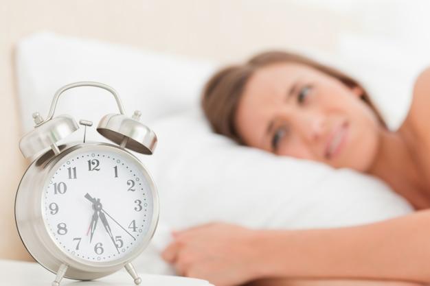 Femme au lit avec son réveil à côté d'elle montrant l'heure