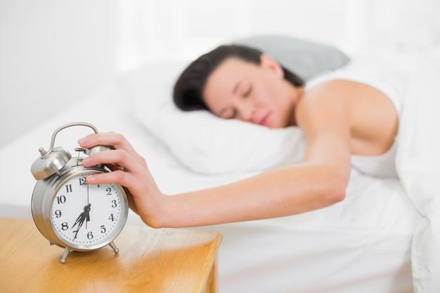 Femme au lit, tendre la main au réveil à la maison